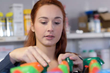 woman organising colorful bottles of spray on shelf