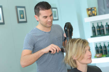 male hairdresser drying womans hair after haircut Zdjęcie Seryjne