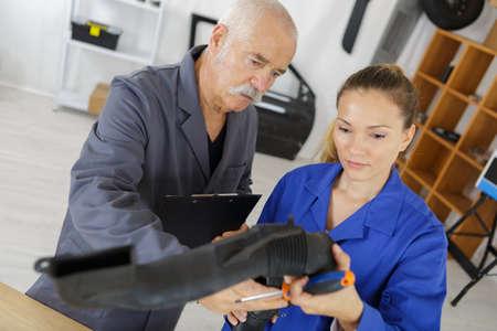 Female apprentice holding mechanical part