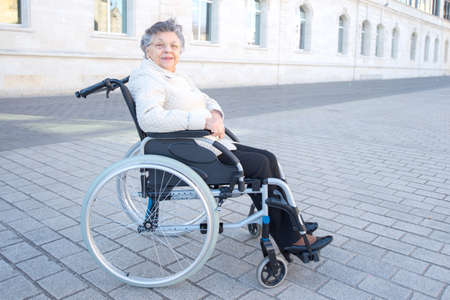 elderly woman on the wheelchair strolling