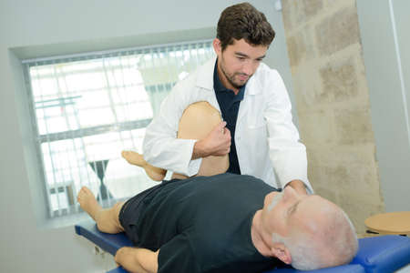 female physio therapist working on male patients leg Stock Photo