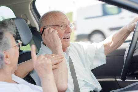 senior woman protesting against her husband driving and calling Stock Photo