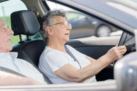 Retired couple in car, woman driving Reklamní fotografie