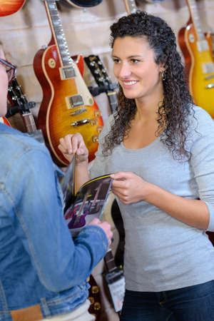 female customer looking for new guitar in store and smiling