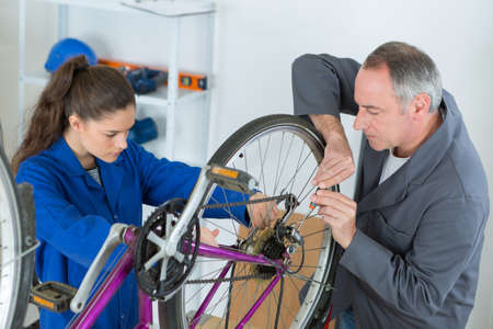 young female apprentice aligning bike tires Stockfoto