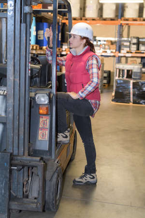 portrait of female fork lift truck driver in factory