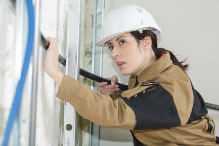 female electrician fitting conduit in wall at construction site Stock Photo