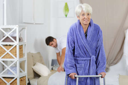 male nurse making bed while female senior using walker