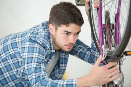 man fixing wheel of bike at home Stock Photo