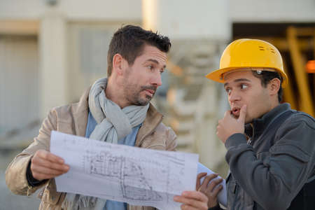male architect with worker discussing at construction site