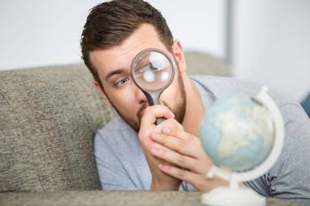 man considering a world globe with a magnifying glass Stock Photo