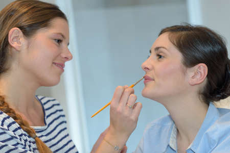 young beautiful woman applying make-up by make-up artist Stock Photo