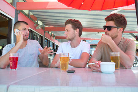 three young men in casual clothes drinking beer
