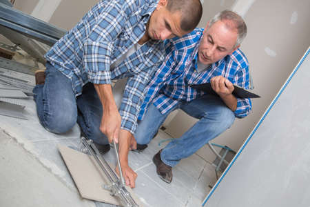 man laying ceramic floor tiles in a new building Stock Photo