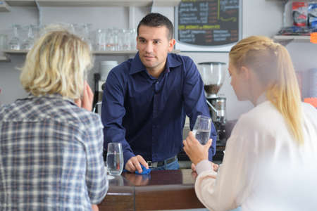 happy smiling women standing at bar and flirting with barman Stock Photo