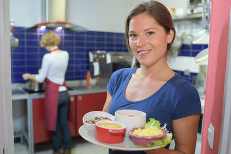 waitress showing dishes to the camera and chef in background