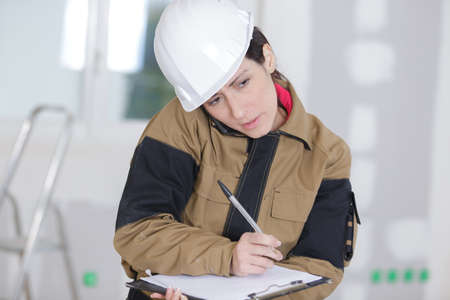 woman builder writes on her clipboard