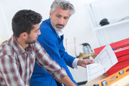 plumber and inspector looking at plans Stock Photo