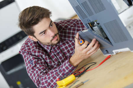 young repairer working with screwdriver in service center Archivio Fotografico