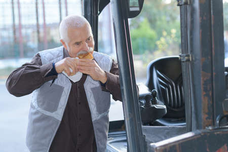 Fork lift driver eating a sandwich Stock Photo
