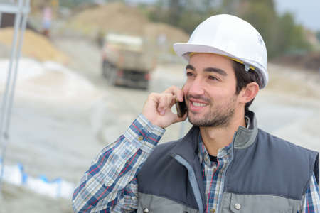 builder in hardhats on the phone outdoors Stock Photo
