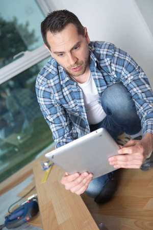 man fitting flooring looking at digital tablet with surprise Stock Photo