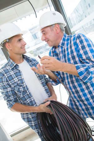 professional electrician with student at construction site