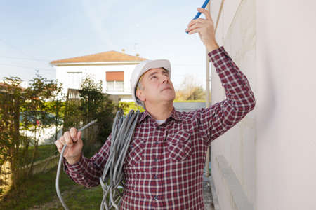 middle-age builder with roll of cable over his shoulder outsied Stock Photo