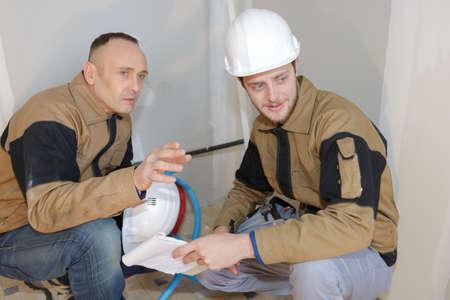 Men crouching down on work site Stock Photo