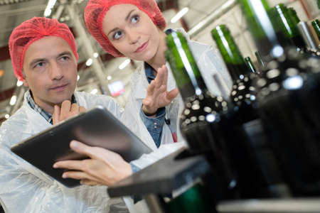 workers looking at tablet pc while working in bottling factory