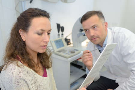 adult male doctor examing female patient