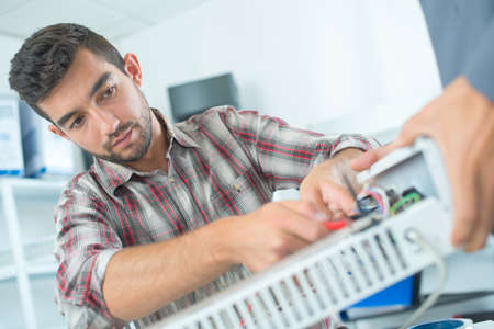 Man working on electrical appliance Stock Photo