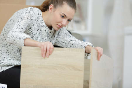 woman assembling furniture at home on the floor