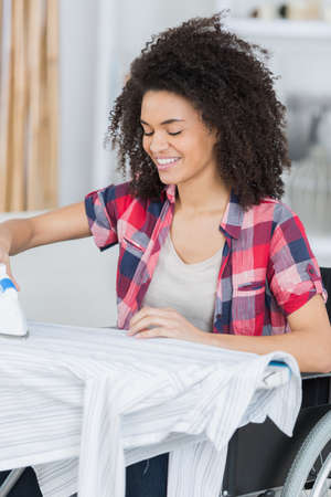 woman on a wheelchair ironing Stock Photo
