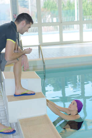 coach talking to swimmer in pool