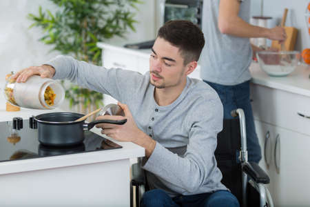 boy in the wheelchair cooking Stock Photo