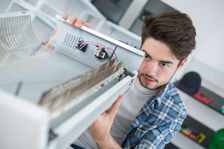man fixing an electric radiator