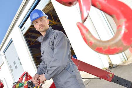 builder operating a crane hook outdoors