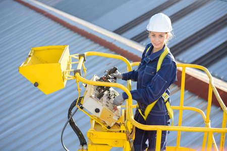 vrouwelijke bouwvakker ter plaatse in hydraulische hijs oprit