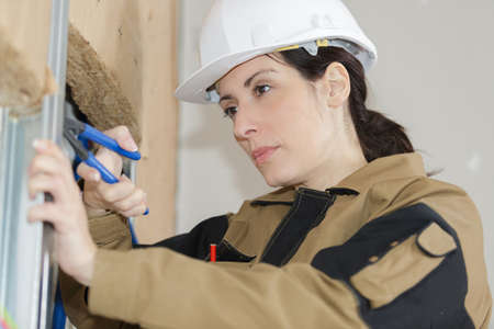 female builder worker on insulation wall