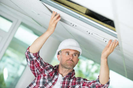 man removing panel on ceiling