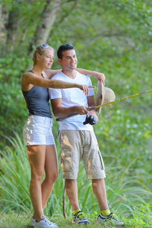 Couple in countryside, man holding fishing rod