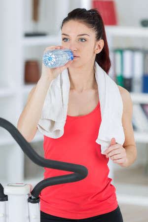 young athletic woman is drinking water after training