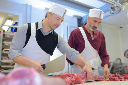 butchers cutting the fresh meat in ham and pork factory Stock Photo