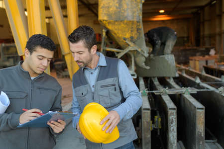 2 workers discussing in metalworks factory Stock Photo