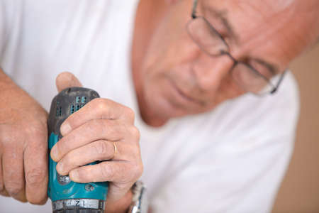 mature using drill in carpentry class Stock Photo