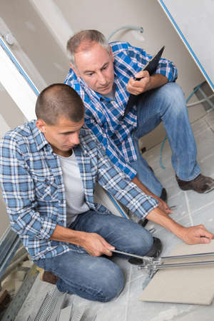 apprentice tile setter cutting the tile