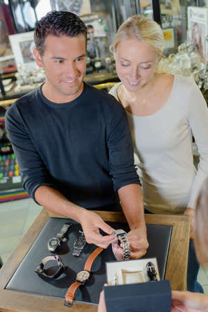 man choosing watches in jewellery store