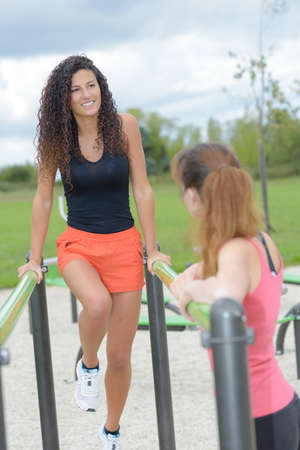 young woman doing pull up exercises in outdoor gym park Stockfoto