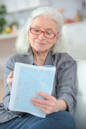 ältere Frau, die Kreuzworträtsel macht